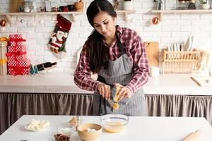 donna latina che versa il miele sull'impasto cucinando in cucina foto