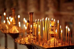 molte lunghe candele accese durante il servizio in chiesa foto