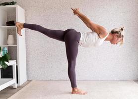 giovane donna attraente che pratica yoga, indossando abbigliamento sportivo foto