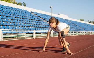donna in posizione di partenza, pronta a correre sulla pista dello stadio foto