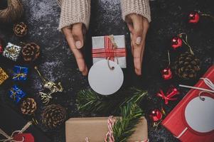 mano che tiene una confezione regalo nera su uno sfondo di gesso nero foto