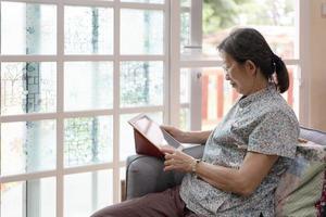 donna matura che usa il tablet per leggere a casa foto