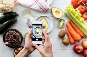 mani femminili che scattano una foto di cibo sano vista dall'alto piatta