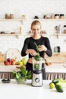 giovane donna bionda sorridente che fa il frullato di spinaci a casa cucina foto