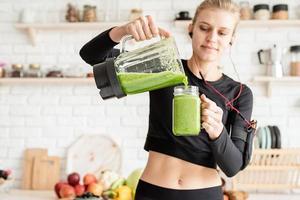 giovane donna sorridente bionda che fa il frullato verde a casa cucina? foto
