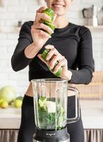 giovane donna bionda sorridente che fa il frullato di cetriolo a casa cucina foto
