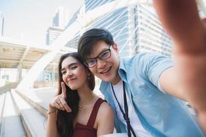 le coppie amano l'uomo e la donna che usano lo smartphone per fare un selfie. foto