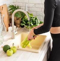 donna che lava il sedano nel lavello della cucina foto