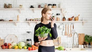 donna in abiti sportivi che tiene una ciotola di spinaci freschi in cucina foto