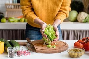 donna che prepara insalata greca in cucina tagliando lattuga foto