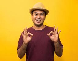 giovane uomo asiatico che mostra il segno giusto della mano su fondo giallo. foto