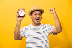 giovane uomo asiatico che tiene la sveglia su sfondo giallo isolato. foto