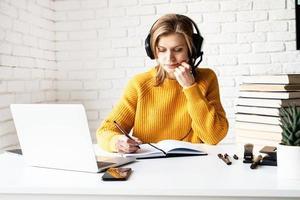 donna che studia online utilizzando il laptop che scrive nel notebook foto