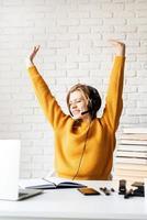donna seduta alla scrivania che si stiracchia dopo un lungo studio foto
