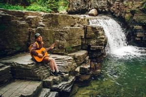 uomo che suona la chitarra seduto vicino a una cascata foto