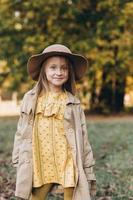 una bambina con un vestito giallo e un cappotto beige cammina nel parco autunnale foto