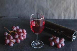 vino rosso e bottiglia di vino con uva su sfondo nero foto