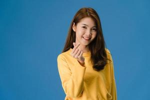 la giovane signora asiatica mostra il gesto delle mani a forma di cuore su sfondo blu. foto