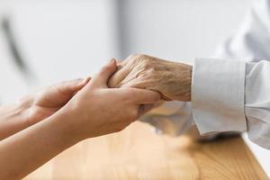 infermiera che tiene le mani dell'uomo anziano comfort. risoluzione e bella foto di alta qualità