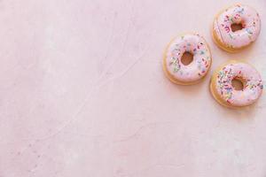 vista dall'alto ciambelle fresche con spruzza sfondo rosa. risoluzione e bella foto di alta qualità