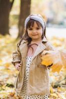 bella bambina che tiene una foglia d'acero gialla nel parco autunnale foto