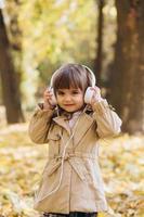 bambina felice che ascolta la musica sulle cuffie nel parco autunnale. foto