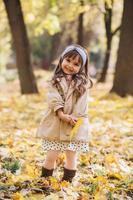 bambina felice che tiene una foglia d'acero gialla nel parco autunnale foto
