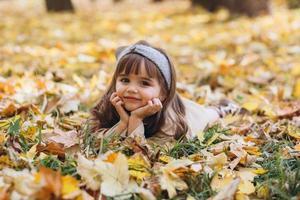 la bambina giace tra le foglie gialle nel parco autunnale foto