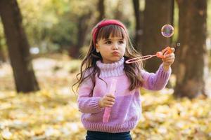 bambina che gioca con bolle di sapone di foglie autunnali nel parco foto