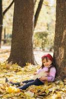 bambina seduta tra le foglie autunnali gialle nel parco foto