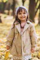 bambina felice che tiene in mano una foglia d'acero gialla nel parco autunnale foto