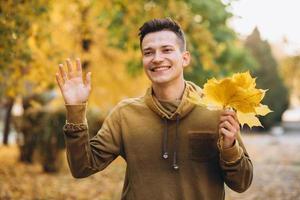 ritratto di un ragazzo bello e felice che sorride e saluta nel parco autunnale foto