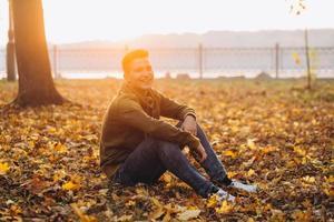 ragazzo bello e felice che sorride nel parco autunnale foto