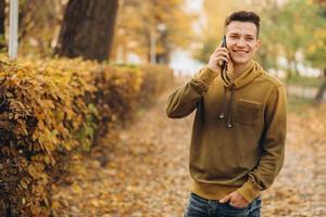 ragazzo felice che sorride e parla al telefono nel parco autunnale foto