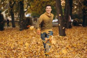 bel ragazzo sorride e corre spargendo foglie gialle nel parco autunnale foto