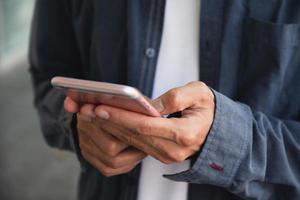 primo piano mano utilizzando smartphone, tecnologia internet del telefono cellulare foto