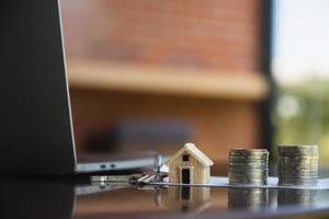 Mutuo per la casa monete pila sul computer tavolo vista laterale sfondo concept foto