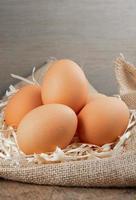 uova biologiche fresche in tela con erba secca su tavola di legno foto