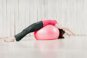 donna che si esercita su palla rosa foto