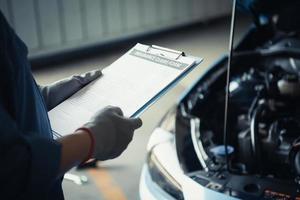 meccanico di auto che tiene appunti e controlla per la manutenzione foto
