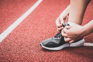 primo piano della donna sportiva che lega la corda del laccio delle scarpe da ginnastica foto