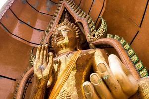 simbolo di crisantemo d'argento e foglia d'oro nel palmo della statua del buddha foto
