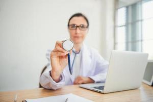 il medico sta esaminando la salute del paziente con lo stetoscopio foto