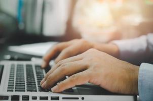 mano dell'uomo utilizzando il computer portatile sul tavolo a casa foto
