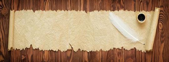 piuma bianca con carta vecchia sul tavolo, vista panoramica foto