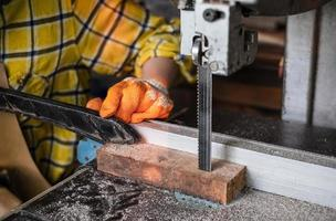 donna che lavora il legno tagliato con seghe a nastro utensili elettrici foto