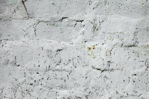 trama di un muro di mattoni con crepe e graffi foto
