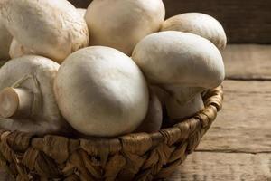funghi champignon in un cesto di vimini su uno sfondo di legno foto