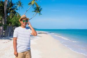 giovane uomo asiatico sulla spiaggia utilizzando smartphone. foto