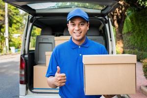 consegna l'uomo in uniforme blu e scatola di cartone per pacchi foto